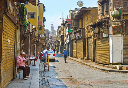 souq: CAIRO, EGYPT - OCTOBER 10, 2014: The elderly merchant reads the morning newspaper in front of his closed stall in Khan el-Khalili souq, on October 10 in Cairo. Editorial