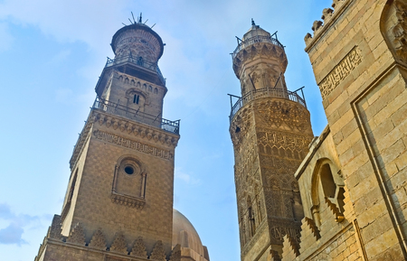 neighboring: CAIRO, EGYPT - OCTOBER 10, 2014: Two neighboring minarets on Al-Muizz street compete in beauty and complexity of the carved decor, on October 10 in Cairo. Editorial