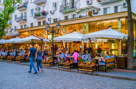 ODESSA, UKRAINE - MAY 17, 2015: The best way to relax in the evening in Odessa is to have a supper in summer terrace in on of the restaurants, on May 17 in Odessa. Publikacyjne