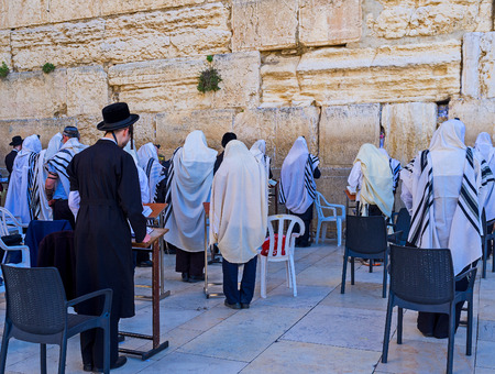 The Hasidic Orthodox jews in traditional clothes and tallits pray at the Western Wall in Ha Kotel Square, Jerusalem, Israel.