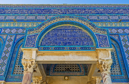JERUSALEM, ISRAEL - FEBRUARY 16, 2016: The side entrance canopy of the Dome of the Rock decorated with the old arabic calligraphy, islamic patterns on the glazed tiles and carved stone pillars, on February 16 in Jerusalem. Editorial