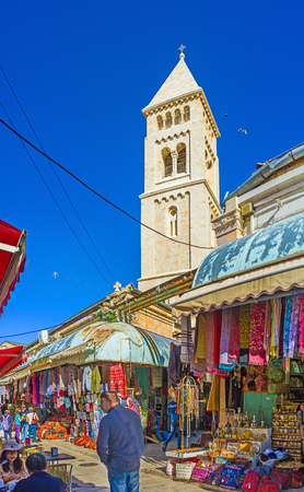 suq: JERUSALEM, ISRAEL - FEBRUARY 16, 2016: The white stone belfry of the Lutheran Kirche rises over the stalls of the Aftimos Suq, on February 16 in Jerusalem.