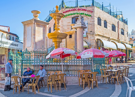 sepulcher: JERUSALEM, ISRAEL - FEBRUARY 16, 2016: The medieval stone drinking fountains on the Muristan Square surrounded by the tables of the local tavern, on February 16 in Jerusalem.