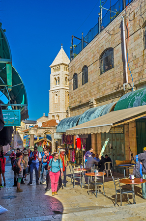 neighboring: JERUSALEM, ISRAEL - FEBRUARY 16, 2016: The Aftimos Suq is the crowded place, tourists often visit it after the neighboring Church of the Holy Sepulchre, on February 16 in Jerusalem.