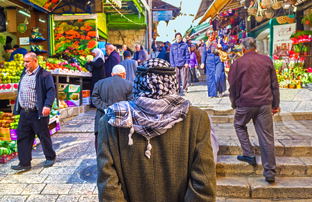 keffiyeh: JERUSALEM, ISRAEL - FEBRUARY 16, 2016: The pensive Palestinian in keffiyeh stands and watches the Arab bazaar at Damascus Gate, on February 16 in Jerusalem.