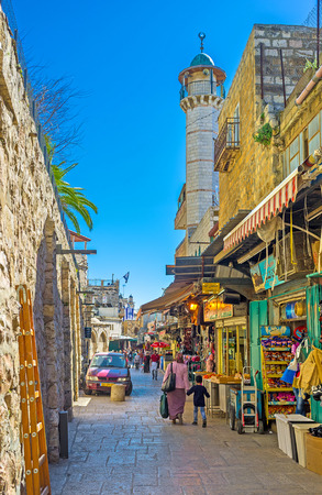damascus: JERUSALEM, ISRAEL - FEBRUARY 16, 2016: The white minaret rises over the bazaar in Muslim Quarter, next to Damascus Gate, on February 16 in Jerusalem. Editorial