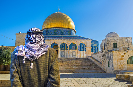 dome of the rock: JERUSALEM, ISRAEL - FEBRUARY 16, 2016: The pensive Palestinian in keffiyeh stands next to the staircase, leading to the Dome of the Rock on the Temple Mount, on February 16 in Jerusalem.