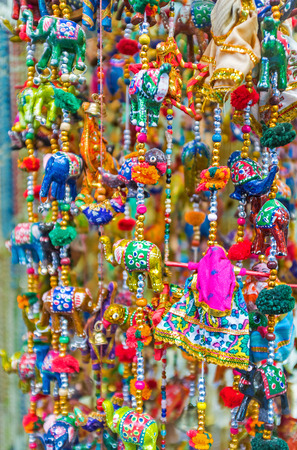 king parrot: The colorful wind chimes with toy elephants, dolls and different beads in market stall, Jerusalem, Israel. Stock Photo