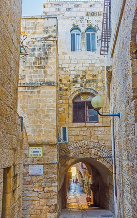 jewish houses: JERUSALEM, ISRAEL - FEBRUARY 16, 2016: The narrow street with the tiny passage through the house in the maze of the Jewish Quarter, on February 16 in Jerusalem