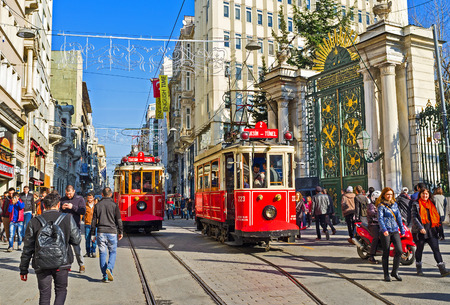 main gate: ISTANBUL, TURKEY - JANUARY 22, 2015: Two red trams stands on the station next to the main gate to the Galatasaray High School, on January 22 in Istanbul. Editorial