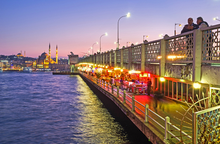 fine fish: ISTANBUL, TURKEY - JANUARY 21, 2015: The bright lights on the ground level of Galata bridge attracts people to the fine fish restaurants and cozy cafes, located there, on January 21 in Istanbul. Editorial
