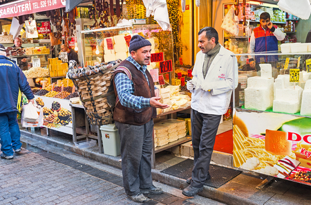 merchant: ISTANBUL, TURKEY - JANUARY 21, 2015: The conversation of the friends - merchant and buyer with the rustic basket on the back, next to the cheese stall, on January 21 in Istanbul.