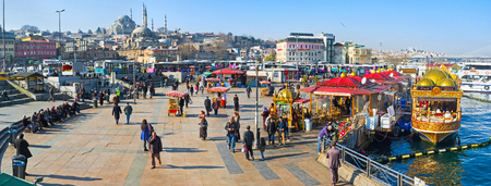 places of interest: ISTANBUL, TURKEY - JANUARY 21, 2015: The Eminonu promenade with floating restaurants, ferry terminal, snack carts and other places of interest, on January 21 in Istanbul.