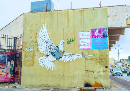 BETHLEHEM, PALESTINE - FEBRUARY 18, 2016: The mural of dove of peace dressed in a body armor with the aim on its heart painted on the wall of the house, on February 18 in Bethlehem. Banco de Imagens - 54317610