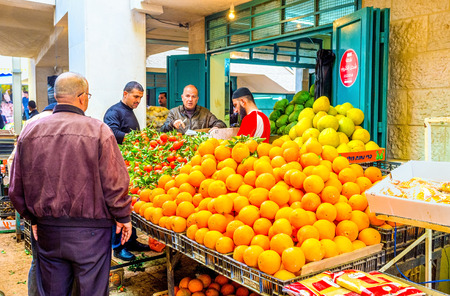 bethlehem: BETHLEHEM, PALESTINE - FEBRUARY 18, 2016: The merchant sells fruits to clients in Bethlehem market, on February 18 in Bethlehem.