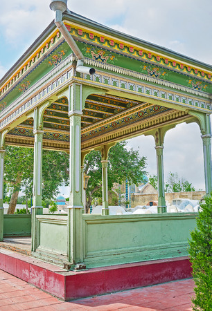 house of prayer: The wooden summer house in cemetery serves as the open air prayer hall, decorated with the colorful patterns, Kokand, Uzbekistan.