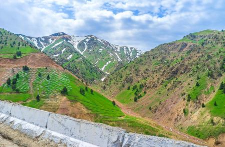 De piek van de Kamchik-pas die met sneeuw wordt behandeld en die door wolken wordt omringd, Oezbekistan. Stockfoto