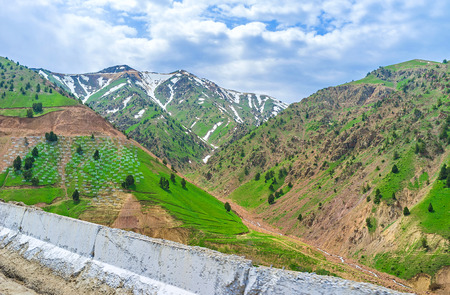 The peak of the Kamchik pass covered with snow and surrounded by clouds, Uzbekistan.