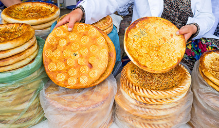 merchant: The merchant demonstrates  lochira (traditional flat bread), that is especially tasty in Fergana Valley region, Pungan, Uzbekistan.