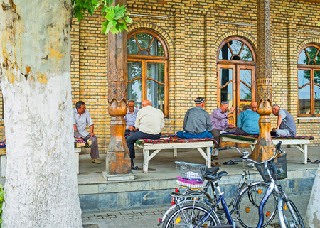 teahouse: KOKAND, UZBEKISTAN - MAY 6, 2015: The elderly men spend their time, playing cards and sitting on the trestle-beds at the summer terrace of traditional teahouse, on May 6 in Kokand.