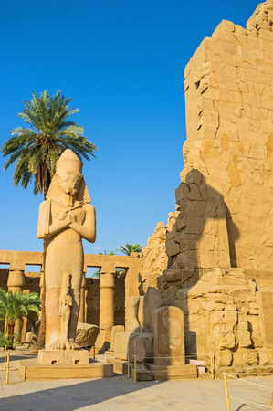 flail: The statue of Ramesses II with crossed arms, holding crook and flail (symbols of kingship), with the small statue of Princess Bent-anta at his fit, Great Court of Karnak Temple, Luxor, Egypt.