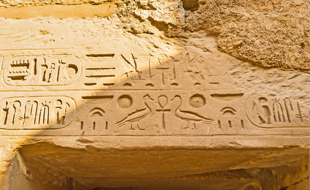 The ancient hieroglyphs over the door in Temple of Ramesses III, include Ankh (Egyptian Cross), geese, mosquitos and other symbols, Karnak Comlex, Luxor, Egypt.