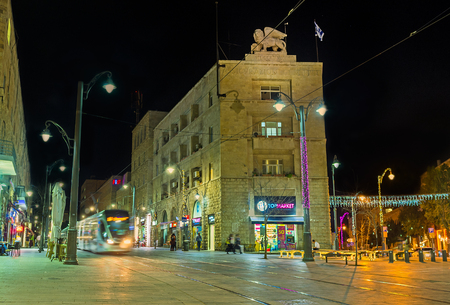leon con alas: Jerusalén, ISRAEL - 17 de febrero, 2016: La noche Yafo Camino con el tranvía, que monta al lado del edificio Generali, decorado con el león alado, el 17 de febrero en Jerusalén. Editorial