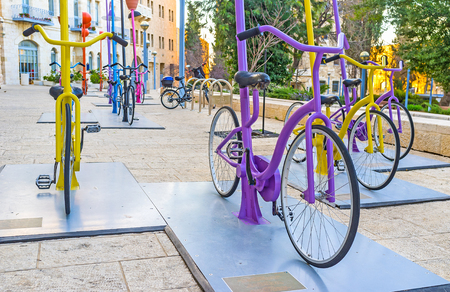 ciclos: JERUSALEM, ISRAEL - FEBRUARY 18, 2016: The rows of colorful cycles in Safra Square attract the tourists and local kids to pedal, on February 18 in Jerusalem.