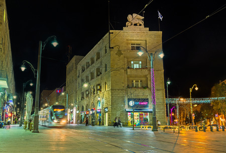 leon con alas: Jerusal�n, ISRAEL - 17 de febrero, 2016: La noche Yafo Camino con el tranv�a, que monta al lado del edificio Generali, decorado con el le�n alado, el 17 de febrero en Jerusal�n. Editorial