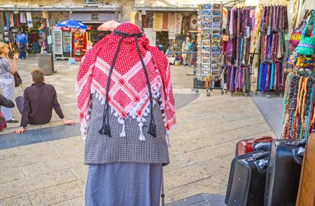 omar: JERUSALEM, ISRAEL - FEBRUARY 18, 2016: The senior Palestinian in red kufiya walks in Omar Ben el-Hatab street along the souvenir shops, on February 18 in Jerusalem.