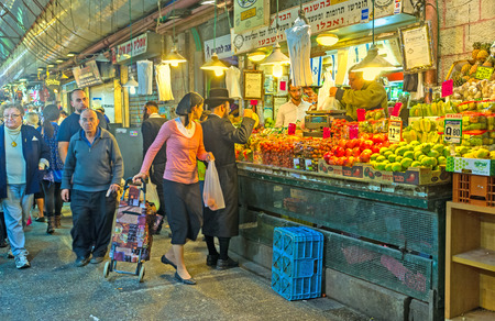 hasid: JERUSALEM, ISRAEL - FEBRUARY 18, 2016: The hasidic family chooses fresh and tasty fruits and vegetables in Mahane Yehuda market, on February 18 in Jerusalem.