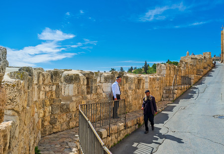 hasid: JERUSALEM, ISRAEL - FEBRUARY 18, 2016: The old Hasid walk along the descent on Batei Mahase street with the view on the medieval city ramparts, on February 18 in Jerusalem.