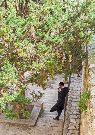 hasid: JERUSALEM, ISRAEL - FEBRUARY 18, 2016: The young hasid relax in shade of the lush pine, leaning on the medieval wall, on February 18 in Jerusalem.