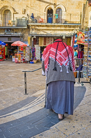 omar: JERUSALEM, ISRAEL - FEBRUARY 18, 2016: The senior Palestinian in traditional red kufiya and galibaya in Omar Ben el-Hatab street, on February 18 in Jerusalem. Editorial