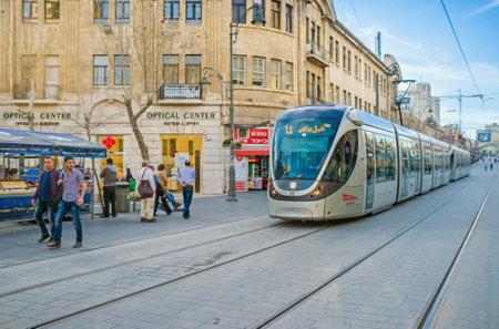 yafo: JERUSALEM, ISRAEL - FEBRUARY 18, 2016: The light rail train rides in Yafo Road, the noisy shopping street, on February 18 in Jerusalem.