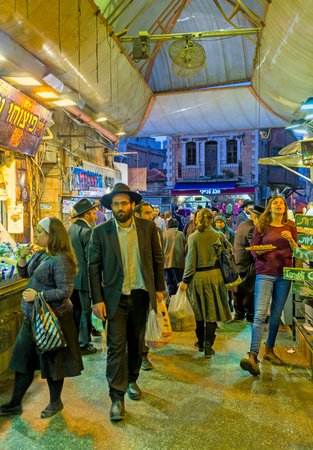 hasid: JERUSALEM, ISRAEL - FEBRUARY 18, 2016: The crowded row of Mahane Yehuda market, the evening is the hot time for the merchants, on February 18 in Jerusalem.