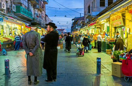 hasid: JERUSALEM, ISRAEL - FEBRUARY 18, 2016: Two friends-hasids, dressed in traditional elegant clothes, talking at the entrance of Mahane Yehuda market, on February 18 in Jerusalem.