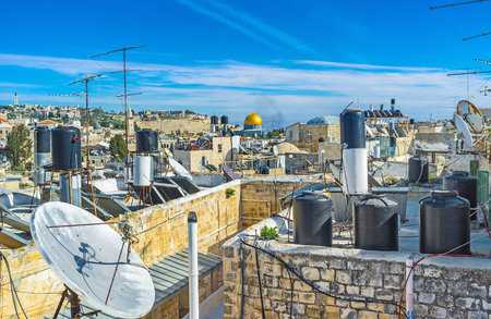 dome of the rock: The golden cupola of the Dome of the Rock between the roofs, water storage tanks and satellites of the residential houses in Jerusalem, Israel.