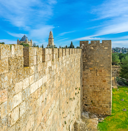 neighboring: The old city wall is neighboring with the Bonei Yerushalayim garden and hides the massive building of Dormition Abbey with the high belfry on the background, Jerusalem, Israel. Stock Photo