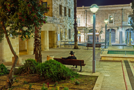 hasid: The hasid has the phone conversation, sitting on the bench in the evening Daniel Park, Jerusalem, Israel. Stock Photo