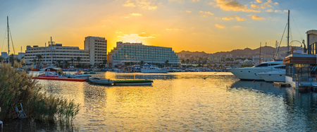 The colorful sunset sky over the Lagoona of Eilat reflects in calm water, Israel.