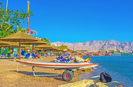 eilat: EILAT, ISRAEL - FEBRUARY 23, 2016: The Hananya Beach with many sunshades, sun beds and the surfboard, on February 23 in Eilat.