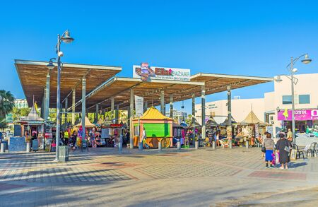eilat: EILAT, ISRAEL - FEBRUARY 23, 2016: The central bazaar with many tourist souvenirs and beach accessories, located on promenade, on February 23 in Eilat.