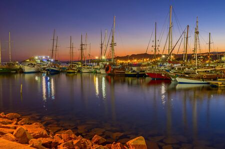 eilat: EILAT, ISRAEL - FEBRUARY 24, 2016: The nice view of the evening port, full of yachts and boats, with the red twilight sky on the background, on February 24 in Eilat.