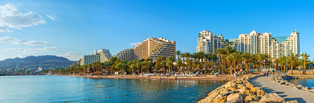 EILAT, ISRAEL - FEBRUARY 24, 2016: The pier is the perfect viewpoint, overlooking the coast of the resort, its central beach, palm gardens and luxury hotels, on February 24 in Eilat. Imagens - 56761615