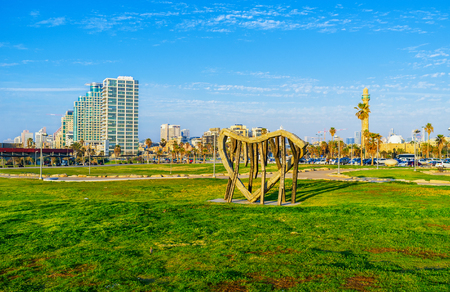 alma: TEL AVIV, ISRAEL - FEBBRUARY 25, 2016: The stone heart installation in Charles Clore Park with the modern city buildings on background, on February 25 in  Tel Aviv.