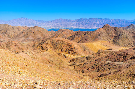 The blue waters of Aqaba Gulf behind the colored Eilat mountains, Israel.