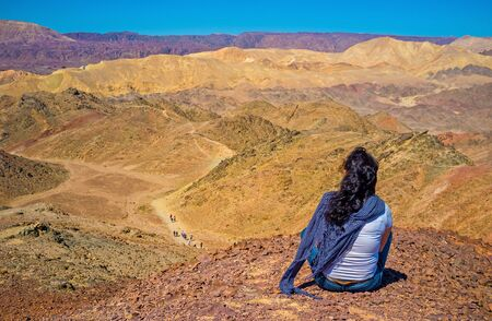 nature reserves of israel: The girl relax after the hiking, sitting on peak of Zefahot Mount and watch the amazing colorful landscapes, Eilat, Israel.