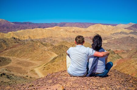 The young couple sits on the top of Zefahot Mount, and gets enjoy of unique views, Eilat, Israel. Stock Photo