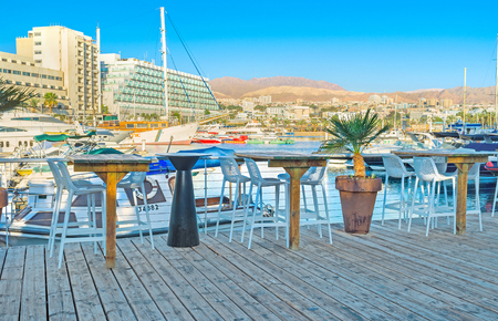eilat: EILAT, ISRAEL - FEBRUARY 23, 2016: The cozy outdoor cafe on the wooden terrace in marina with the view on the white yachts, on February 23 in Eilat.